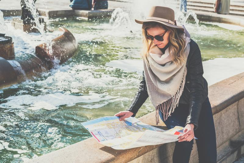 Young female tourist in hat and sunglasses is sitting on street of European city near fountain,holding destination map. Girl is traveler looking for way on map royalty free stock photos