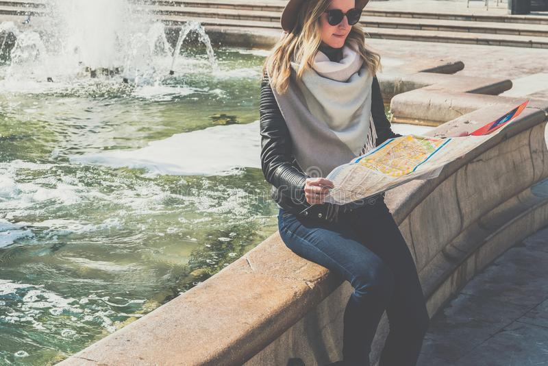 Young female tourist in hat and sunglasses is sitting on street of European city near fountain,holding destination map. Girl is traveler looking for way on map stock images