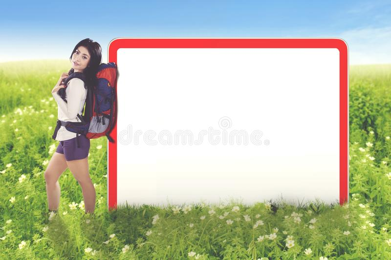 Young female tourist with empty board. Young female tourist holding a backpack while leaning on an empty board. Shot in the blossom meadow stock images
