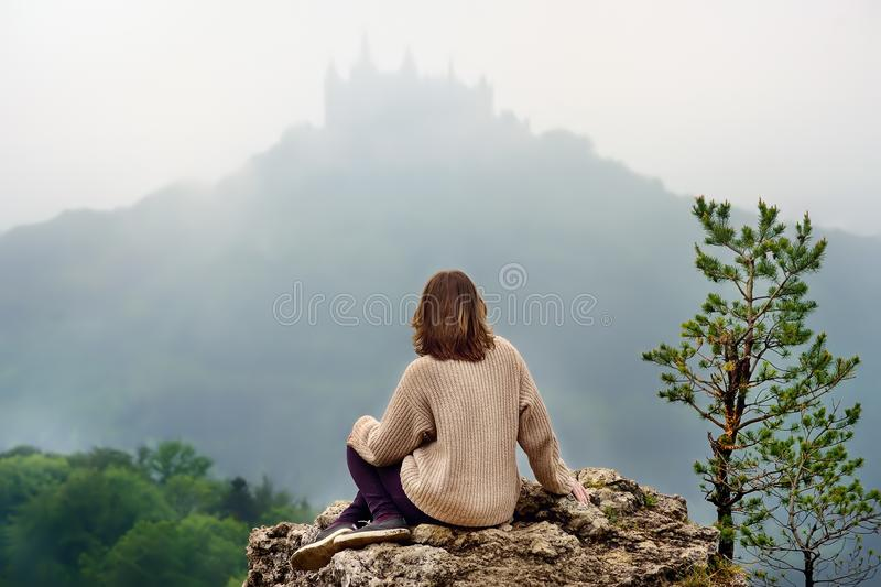 Young female tourist looking on famous Hohenzollern Castle in thick fog, Germany royalty free stock photography