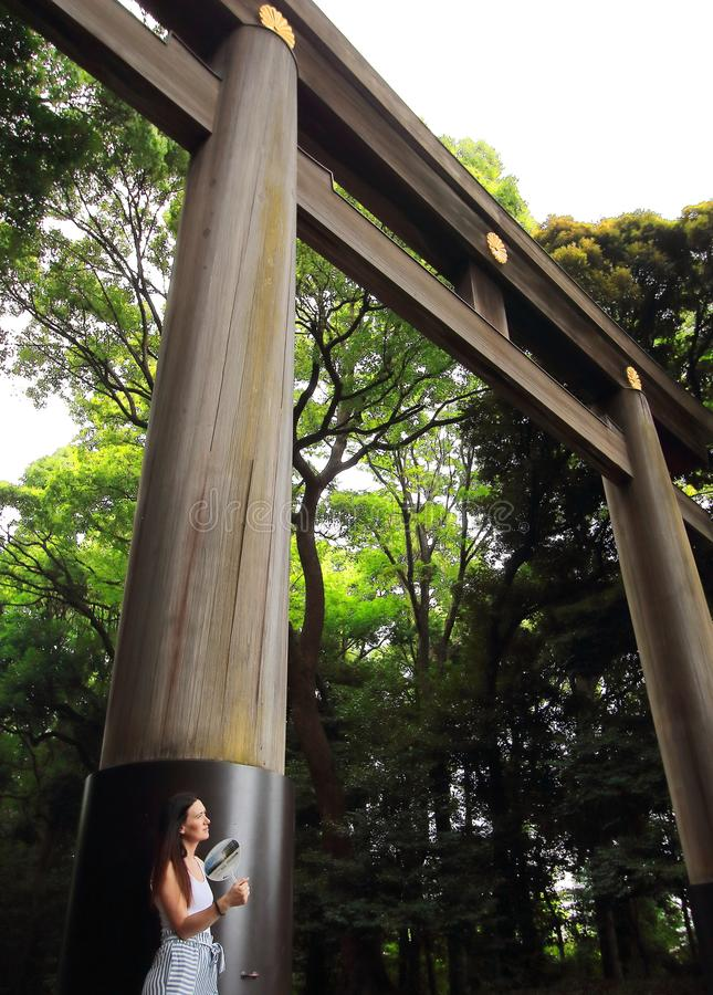 A young female tourist resting under the big torii placed in one of the entrances of Meiji-Jingu temple in Tokyo royalty free stock image