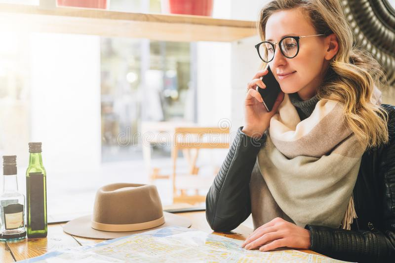 Young female tourist is sitting in cafe at table and talking on cell phone. Girl is calling her friend. Tourism, travel. Young female tourist in eyeglasses is stock photo