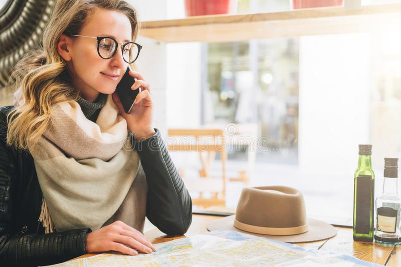 Young female tourist is sitting in cafe at table and talking on cell phone. Girl is calling her friend. Tourism, travel. Young female tourist in eyeglasses is stock image