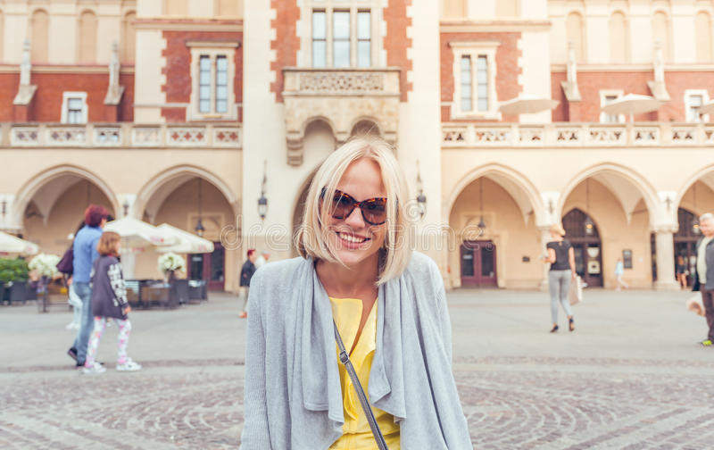 Young female tourist sitting near Cloth Hall in the old city center of Krakow royalty free stock photos