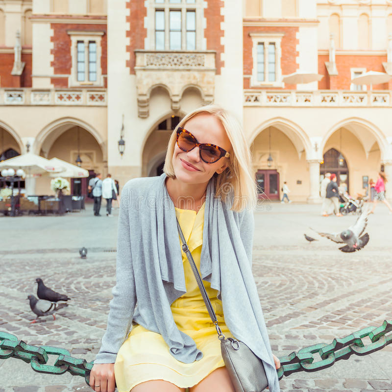Young female tourist sitting near Cloth Hall in the old city center of Krakow stock photography