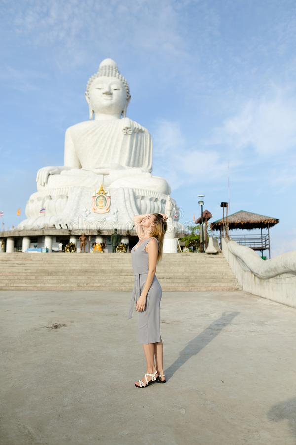 Young female tourist standing near concrete statue of Buddha in Phuket. stock photos