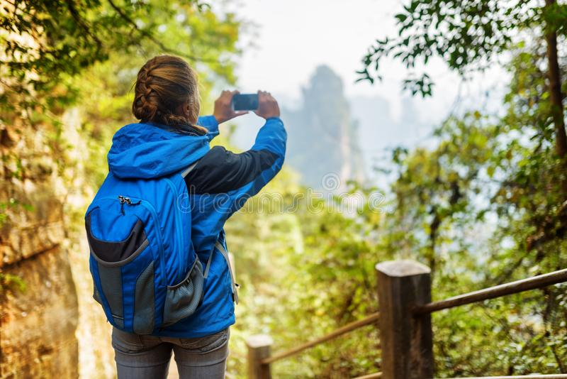 Young female tourist taking photo of beautiful mountain view. Young female tourist with blue backpack among green foliage taking photo of beautiful mountain view royalty free stock images