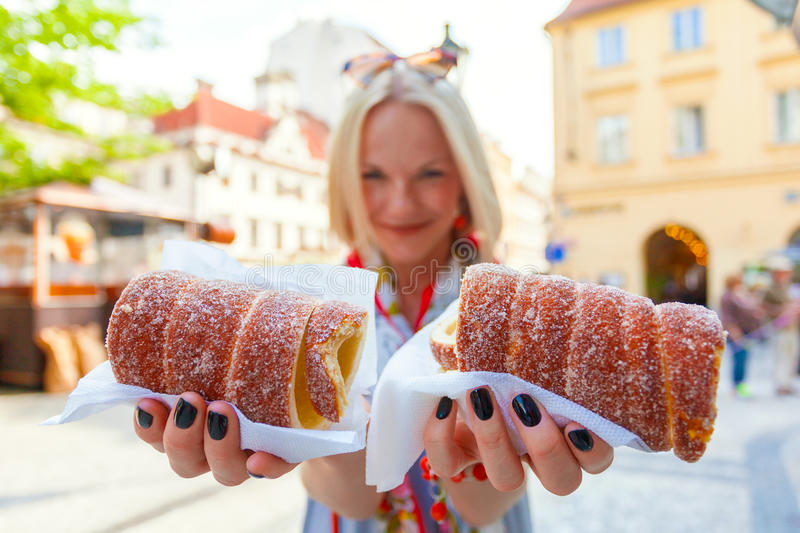 Young female tourist with traditional czech dessert called trdelnik. Prague. Young female tourist with traditional czech dessert called trdelnik in Prague. Czech royalty free stock images