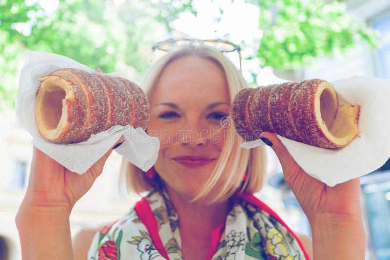 Young female tourist with traditional czech dessert called trdelnik. Prague. Young female tourist with traditional czech dessert called trdelnik in Prague. Czech royalty free stock photos