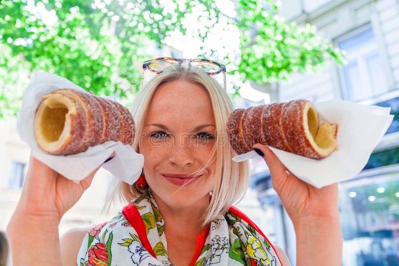 Young female tourist with traditional czech dessert called trdelnik. Prague. Young female tourist with traditional czech dessert called trdelnik in Prague. Czech royalty free stock image