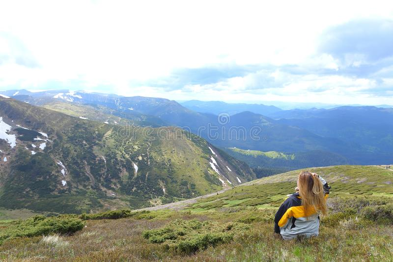 Young female tourist wearing yellow jacket standing in Alps mountains. Young female tourist wearing yellow jacket standing in mountains. Concept of spending royalty free stock images