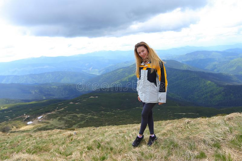 Young female tourist wearing yellow jacket standing in Alps mountains. Young female tourist wearing yellow jacket standing in mountains. Concept of spending stock images