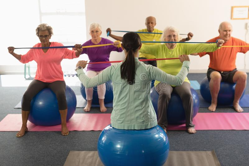 Young female trainer and senior people exercising with resistance band royalty free stock photo