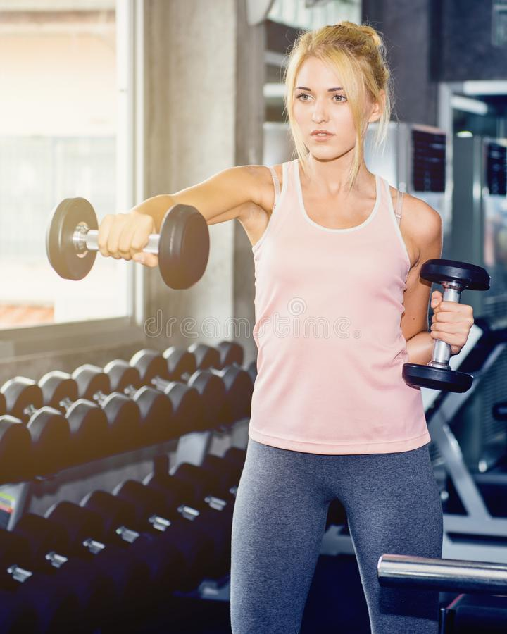 Young female training with dumbbell. In the gym royalty free stock photos