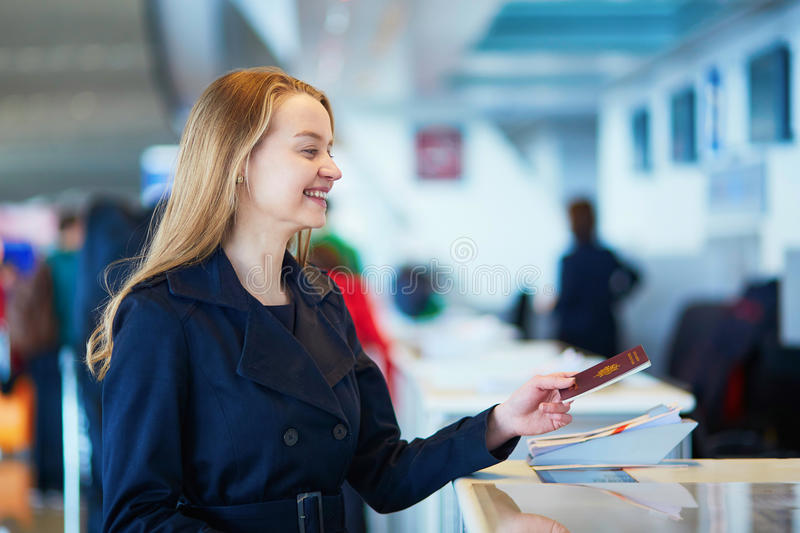Young female traveler in international airport. Young woman in international airport at check-in counter, giving her passport to an officer and waiting for her royalty free stock photo
