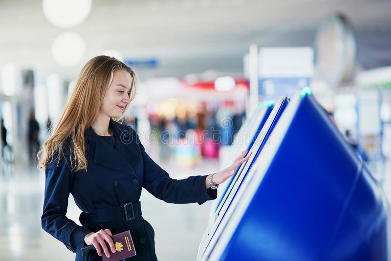 Young female traveler in international airport. Young woman in international airport doing self check-in royalty free stock images