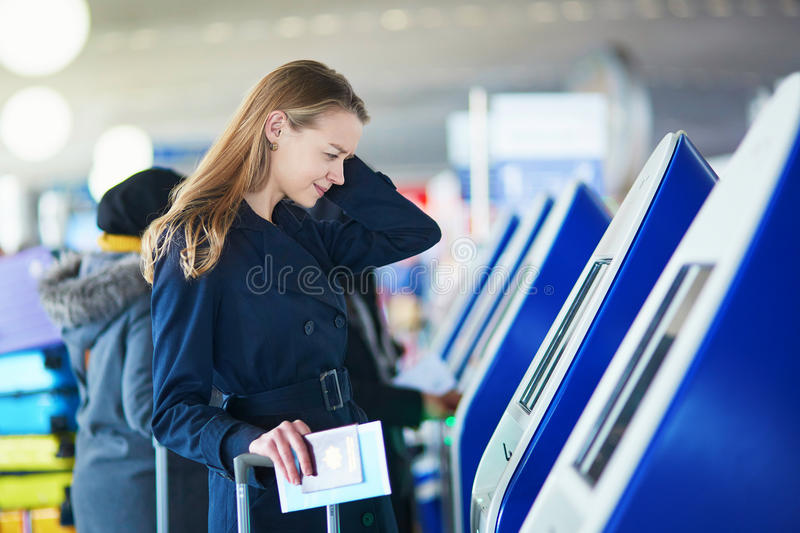 Young female traveler in international airport. Young woman in international airport doing self check-in, stressed and concerned. Missed, delayed or canceled stock photography