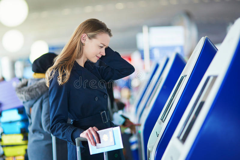 Young female traveler in international airport. Young woman in international airport doing self check-in, stressed and concerned. Missed, delayed or canceled royalty free stock photos