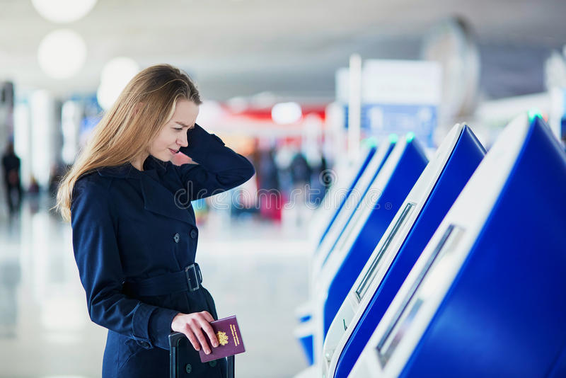 Young female traveler in international airport. Young woman in international airport doing self check-in, stressed and concerned. Missed, delayed or canceled royalty free stock images