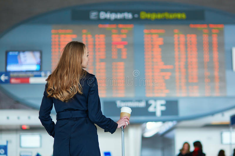 Young female traveler in international airport. Young woman in international airport looking at the flight information board, checking her flight, holding in her stock photo