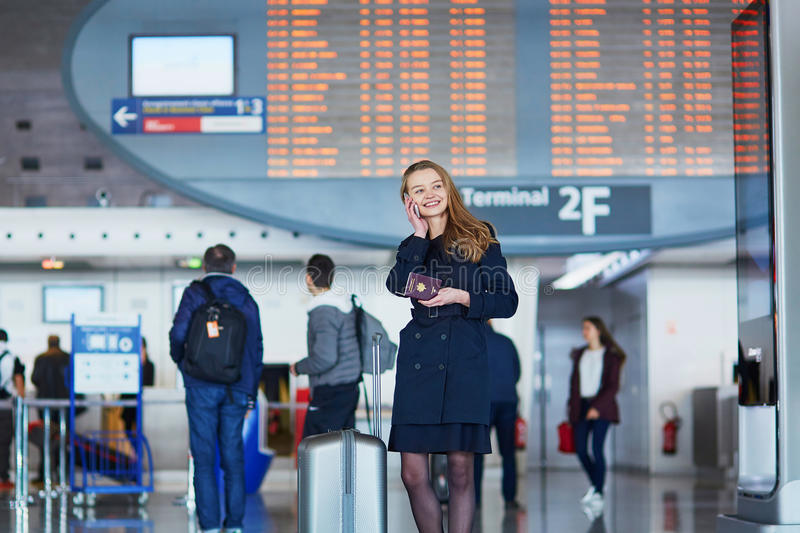 Young female traveler in international airport. Young woman in international airport near the flight information board, holding French passport in her hand and royalty free stock photography