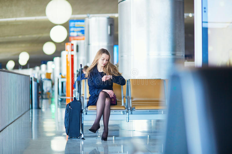 Young female traveler in international airport. Young woman in international airport, waiting for her flight, checking her watch and looking upset or worried royalty free stock image