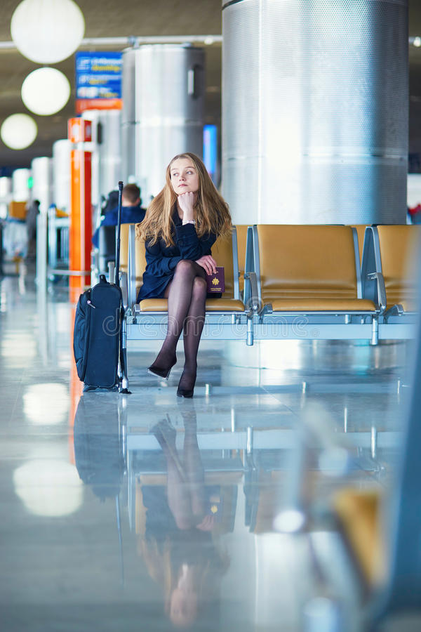 Young female traveler in international airport. Young woman in international airport, waiting for her flight, looking upset or worried. Missed, canceled or royalty free stock images