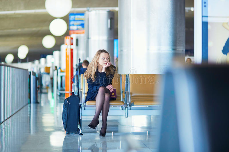 Young female traveler in international airport. Young woman in international airport, waiting for her flight, looking upset or worried. Missed, canceled or stock photos