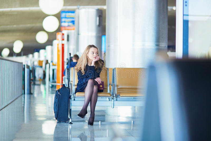 Young female traveler in international airport. Young woman in international airport, waiting for her flight, looking upset or worried. Missed, canceled or royalty free stock photo