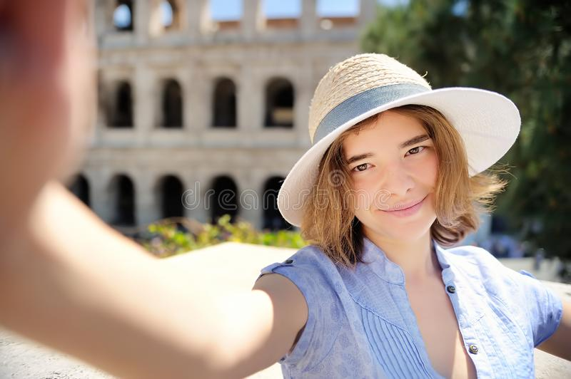 Young female traveler making selfie photo standing the Colosseum in Rome, Italy royalty free stock image