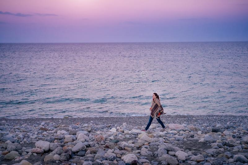 Female traveler taking a walk along the sea shore in Cirali. Young female traveler walking along the pebble beach at the sunset in Turkey royalty free stock images