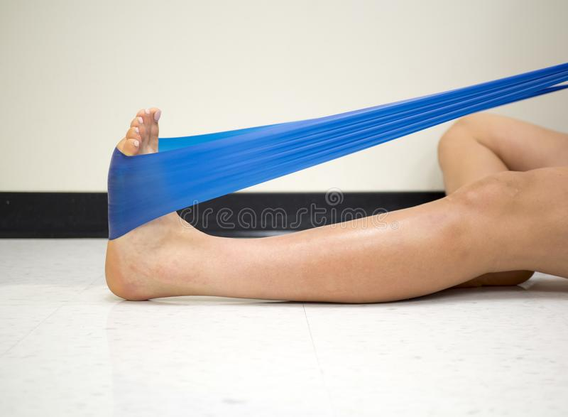 Young Female using a resistance band for ankle exercises in the gym royalty free stock photos