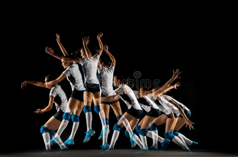 Young female volleyball player isolated on black studio background. Woman in sport`s equipment and shoes or sneakers training and practicing. Concept of sport stock photography