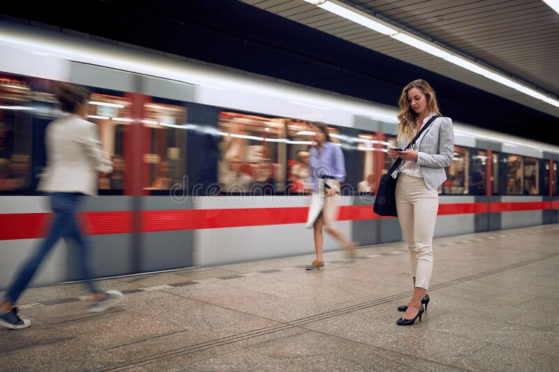 Young female watching at her cell phone in a subway with people and train goes by. Time concept royalty free stock photography