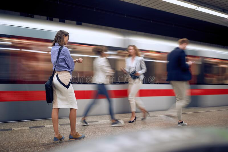 Young female watching at her wrist watch in a subway with people and train goes by stock photo