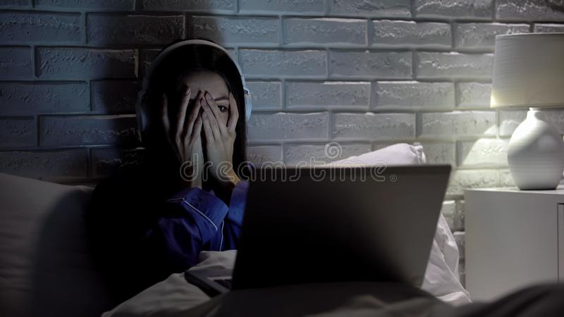 Young female watching scary movie, hiding face in fear, online film service stock photo