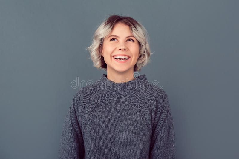Young woman in a grey sweater studio picture isolated on grey background looking up royalty free stock photography