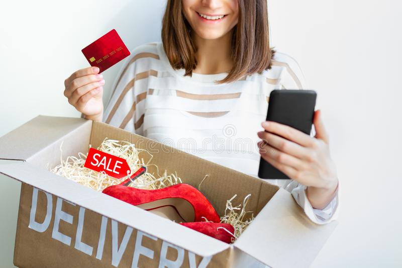 Young female woman adult customer buyer smiling received purchased new red high heels with sale label in delivery box ordered in stock photos