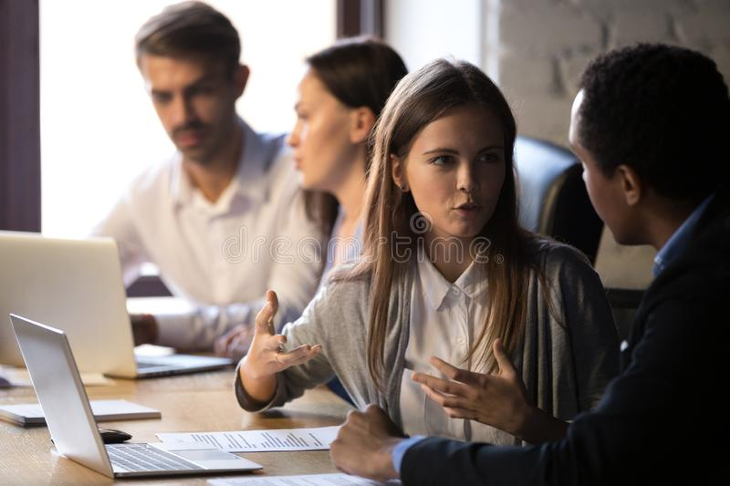 Young female worker speaking to male african colleague explainin royalty free stock photography
