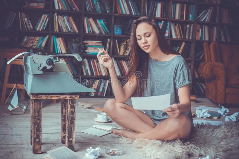 Young woman writer in library at home creative occupation smoking reading. Young female writer in library indoors working smoking reading page of new book royalty free stock image