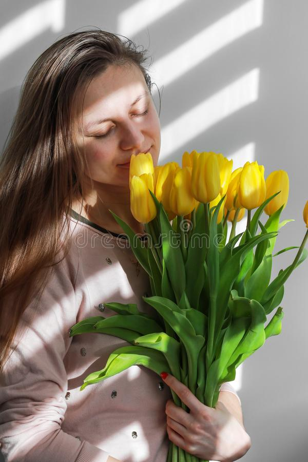 Woman with tulips. Young female with yellow flowers tulip natural portrait lifestyle near white background. Young female with yellow flowers tulip natural royalty free stock photo