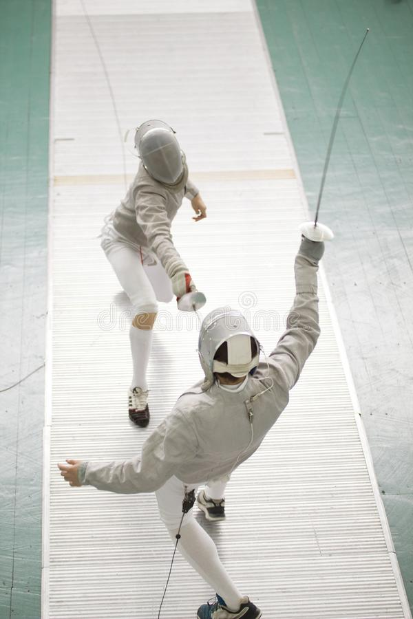 Young fencers in protective costumes fighting on the fencing competition stock photo