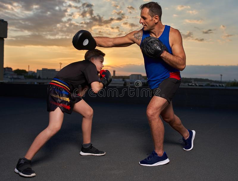 Young fighter hitting pads with trainer at sunset. Young fighter hitting mitts with his coach at sunset on the roof royalty free stock images
