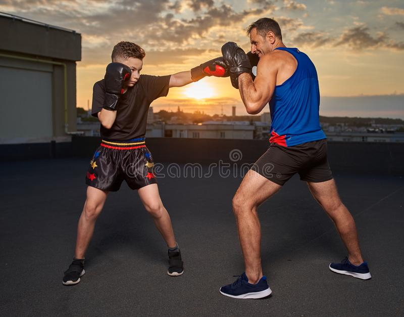 Young fighter hitting pads with trainer at sunset. Young fighter hitting mitts with his coach at sunset on the roof royalty free stock photography