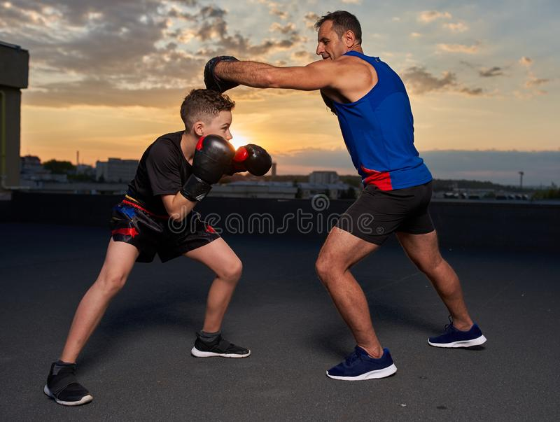 Young fighter hitting pads with trainer at sunset. Young fighter hitting mitts with his coach at sunset on the roof stock photo