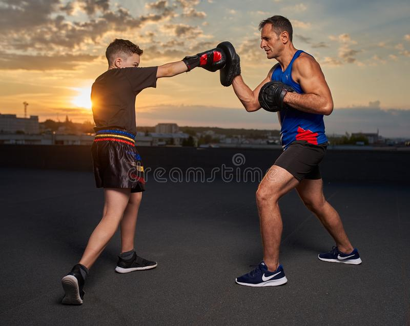 Young fighter hitting pads with trainer at sunset. Young fighter hitting mitts with his coach at sunset on the roof royalty free stock photo