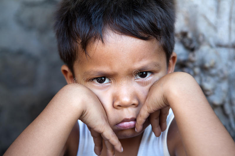Young Filipino boy - poverty. Young Filipino boy with sad expression against wall - poverty in the Philippines royalty free stock images