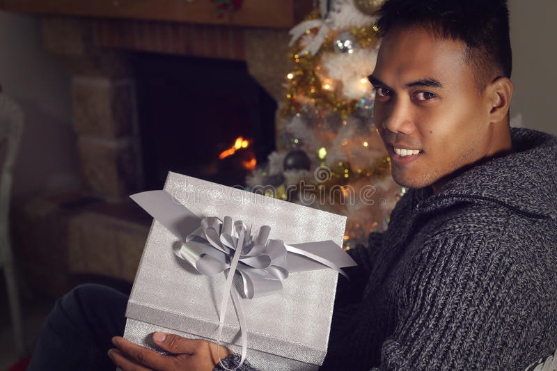 Young Filipino holding a Christmas present. Next to a fireplace stock image