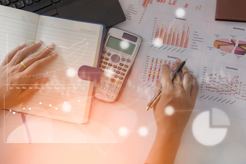 Young finance market analyst working at office on laptop while sitting at white table.Businessman analyze document. And the calculator in hands.Graphs and royalty free stock images