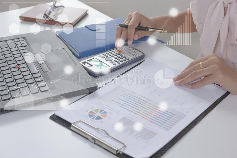 Young finance market analyst working at office on laptop while sitting at white table.Businessman analyze document. And the calculator in hands.Graphs and stock photography